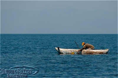 A local fisherman casting his net from a dugout canoe